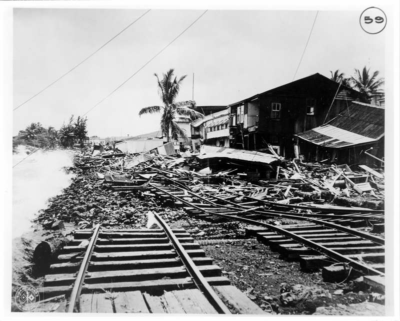 Wreckage of railroad tracks and buildings near shore