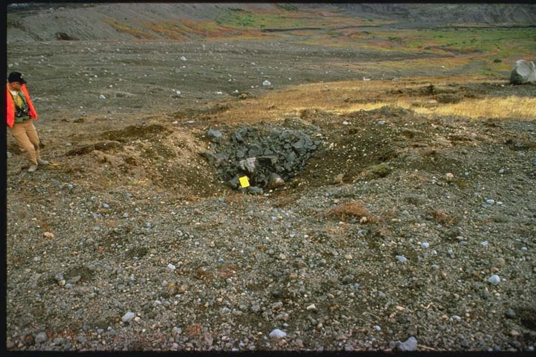 Geologist near one of bomb craters on south flank of Crater Peak